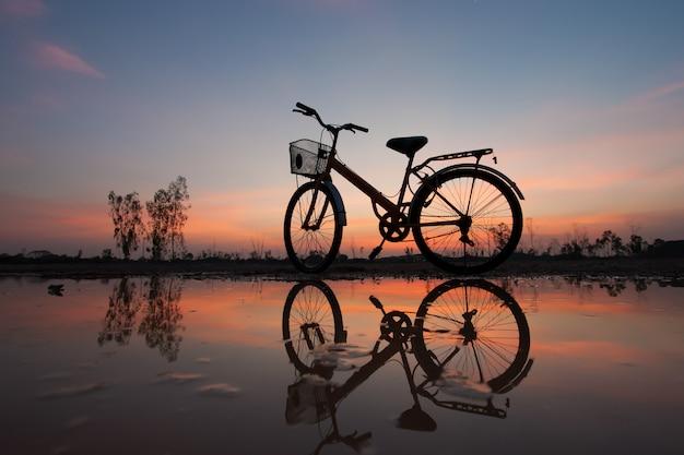 Bicicletta della siluetta al tramonto e alla riflessione