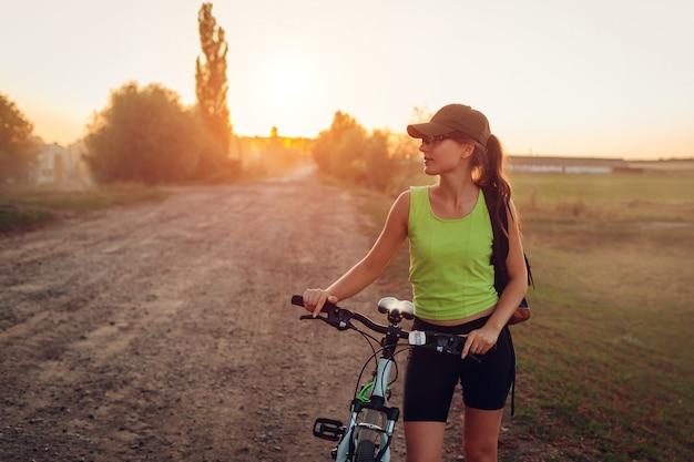 Bicicletta di guida del giovane ciclista felice della donna in periferia.