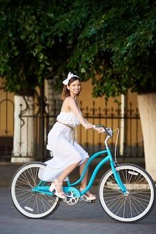 Bicicletta di guida della giovane donna
