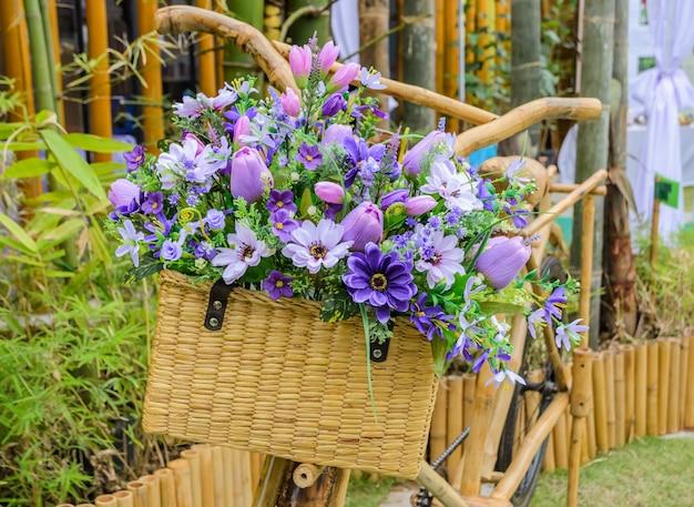 Bicicletta di legno dell'annata con i fiori sul cestino