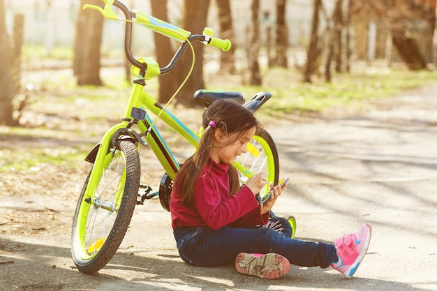 Bicicletta di viaggio del bambino nel parco di estate. orologio della bambina del ciclista sul telefono cellulare. il bambino conta il polso dopo l'allenamento sportivo e sta cercando il modo per navigare.