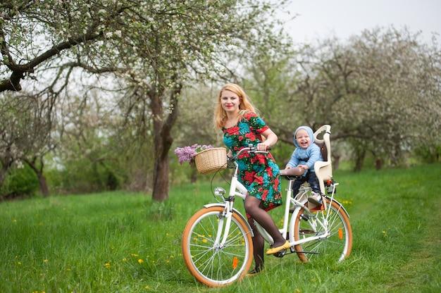 Bicicletta femminile bionda della città di guida con il bambino nella sedia della bicicletta