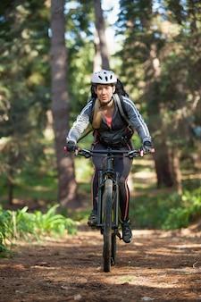 Bicicletta femminile di guida del ciclista in mountain-bike nella foresta