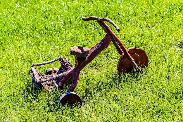 Bicicletta in legno decorativa su erba verde