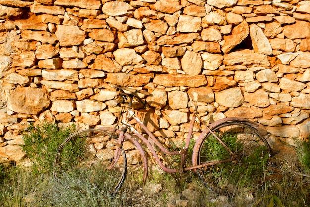 Bicicletta invecchiata arrugginita sul muro di pietra romantica malinconia