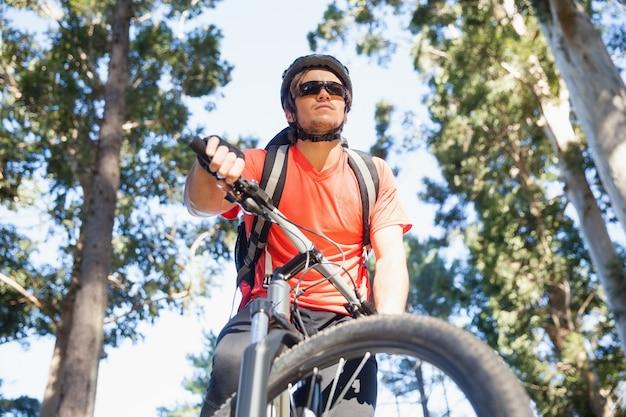 Bicicletta maschio di guida del ciclista in mountain-bike nella foresta