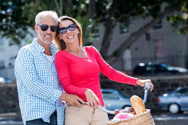 Bicicletta matura felice di guida delle coppie in città