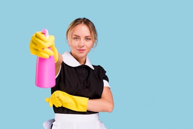 Bidello femminile sorridente che mostra la bottiglia rosa dello spruzzo che esamina macchina fotografica che sta contro la parete blu