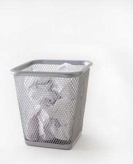 Bidone della spazzatura del metallo, recipiente con carta sgualcita, isolato