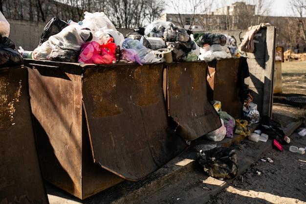 Bidoni della spazzatura con immondizia. cassonetti pieni di spazzatura
