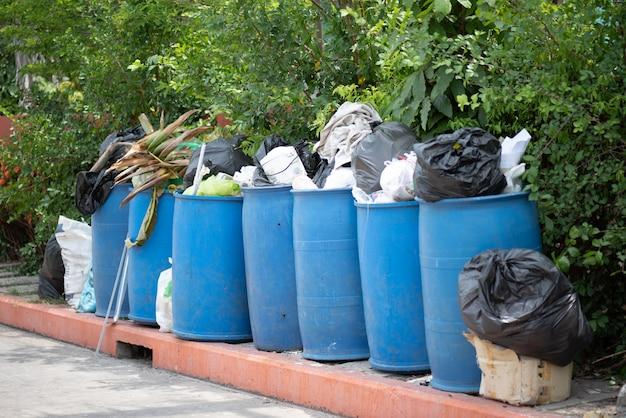 Bidoni della spazzatura straripanti con i rifiuti domestici in città