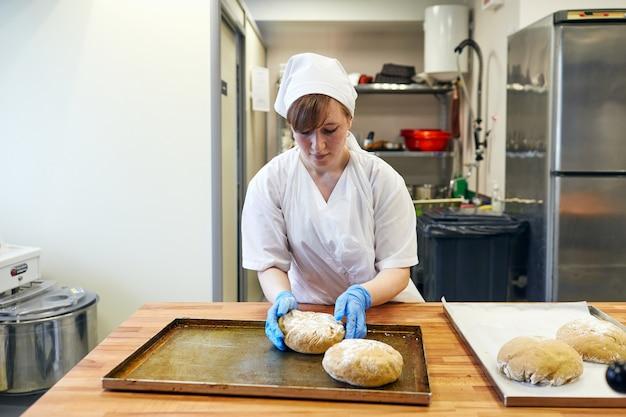 Bielorussia, minsk, 01.20.2020, una cuoca prepara un impasto per il pane, una panetteria