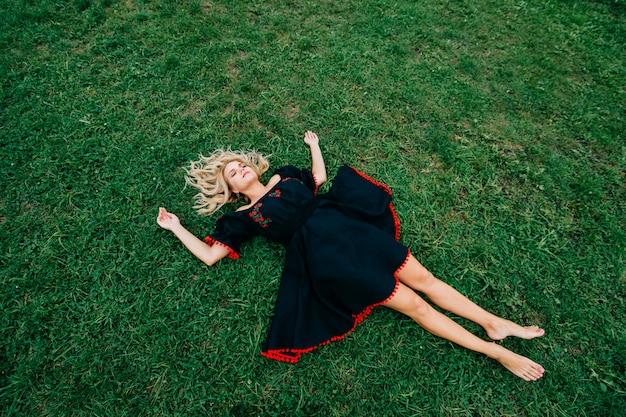 Biew superiore di bella donna bionda in vestito nero che si trova sull'erba verde
