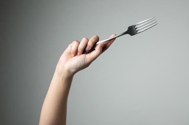 Biforchi con la mano sulla cucina grigia dell'utensile del fondo per cucinare
