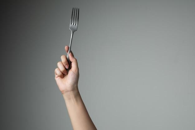 Biforchi con la mano sulla cucina grigia dell'utensile per cucinare