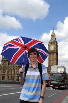 Big ben e turistico con la bandiera britannica ombrello a londra