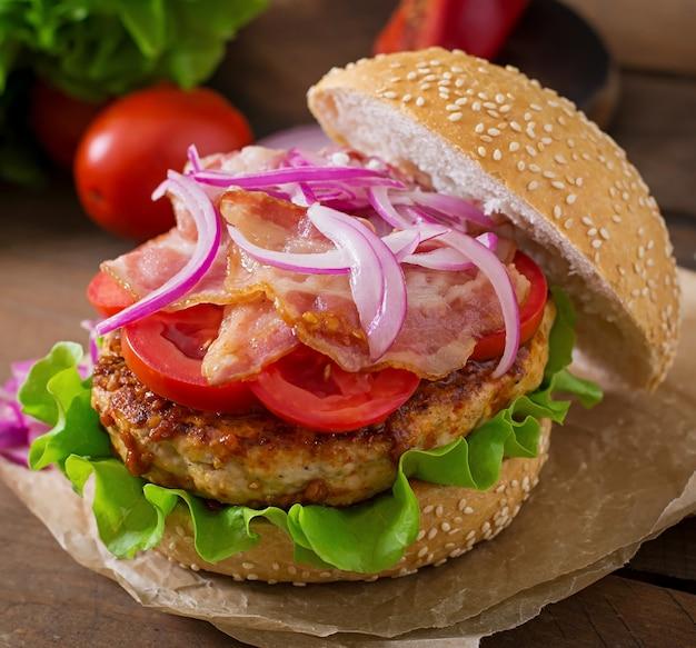 Big sandwich - hamburger con carne di manzo, cipolla rossa, pomodoro e pancetta fritta.