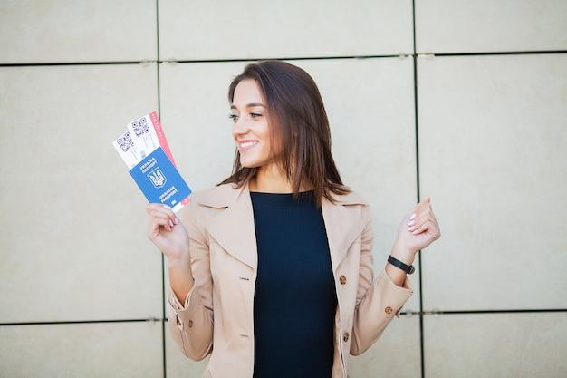 Biglietti aerei della tenuta della donna di affari. viaggiatore che cammina nel corridoio dell'aeroporto
