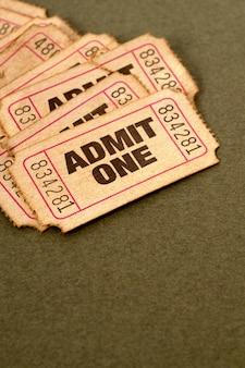 Biglietti ammissione macchiati e danneggiati su uno sfondo di carta marrone chiazzato.