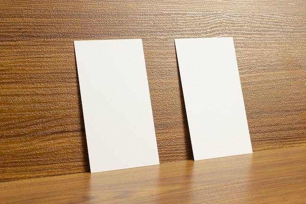 Biglietti da visita bianchi bloccati su una scrivania in legno testurizzato, dimensioni 3,5 x 2 pollici