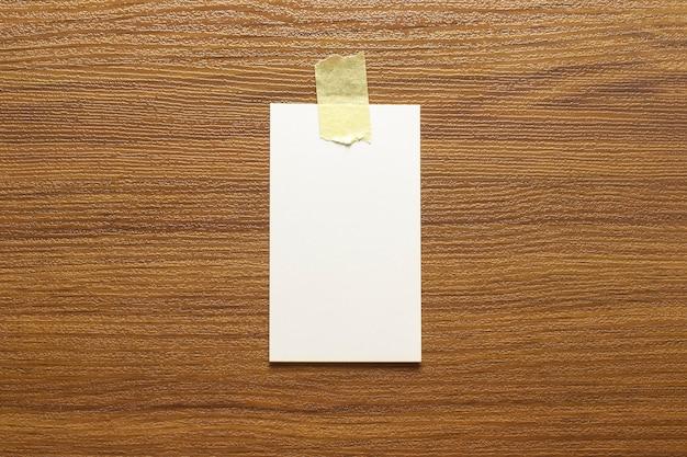 Biglietti da visita bianchi incollati con nastro giallo su una superficie di legno e spazio libero, dimensioni 3,5 x 2 pollici