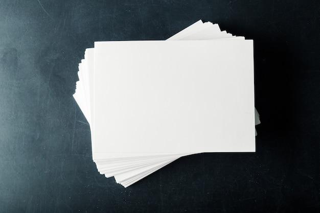 Biglietti da visita in bianco di carta sostenuti sulla pila