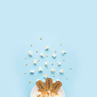 Biglietti del cinema e popcorn su sfondo blu