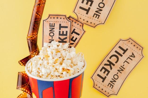 Biglietti del cinema, strisce di pellicola e popcorn sul blu