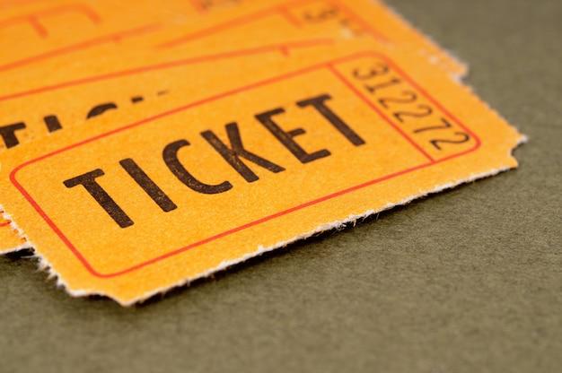 Biglietti di ammissione arancione su uno sfondo di carta marrone chiazzato.