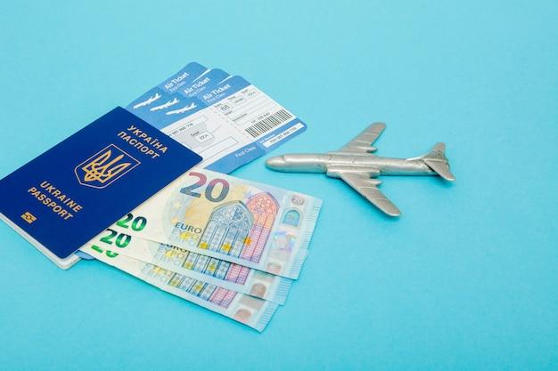 Biglietti per aereo e passaporto, euro con modello di aereo sul blu