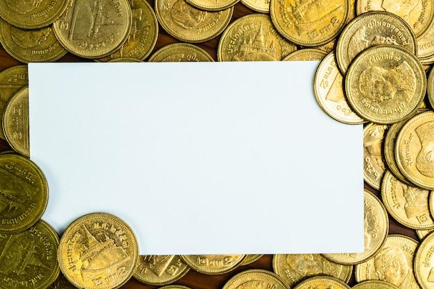 Biglietto da visita in bianco o carta di nome e pila di monete