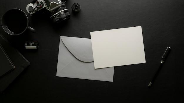 Biglietto di auguri con busta grigia sulla scrivania scura con fotocamera digitale e forniture per ufficio