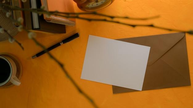 Biglietto di auguri con busta marrone sul piano di lavoro creativo con libri e decorazioni
