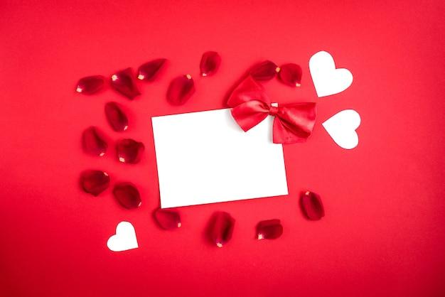 Biglietto di auguri con fiocco rosso e petali di rosa su fondo rosso.