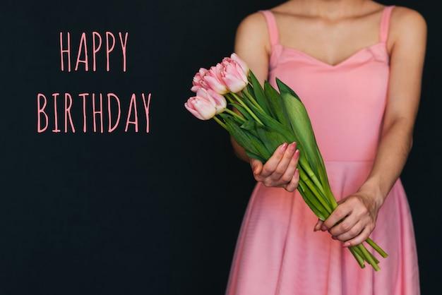 Biglietto di auguri con la scritta buon compleanno. mazzo di tulipani rosa nelle mani