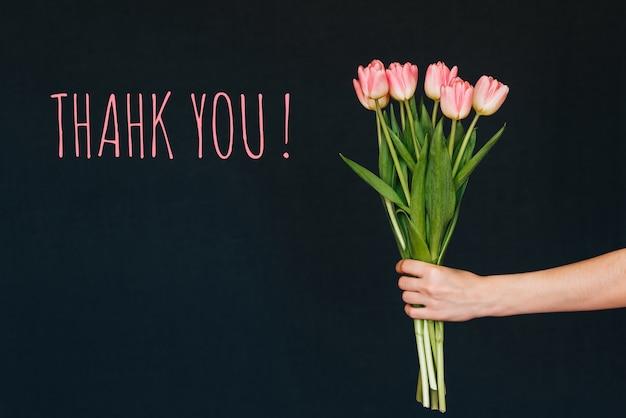 Biglietto di auguri con la scritta grazie. mazzo dei fiori rosa del tulipano in mano di una donna