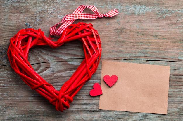 Biglietto di auguri con un cuore rosso e spazio per il testo su uno sfondo di legno