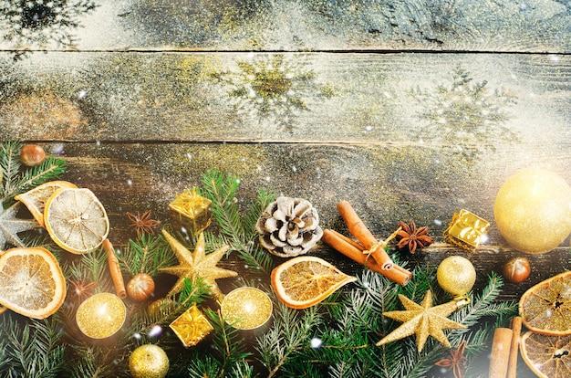 Biglietto di auguri di natale con doni, candele, coni, bastoncini di cannella, arancio secco, albero verde