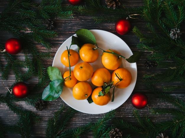 Biglietto di auguri di natale con mandarini e rami di abete e pigne