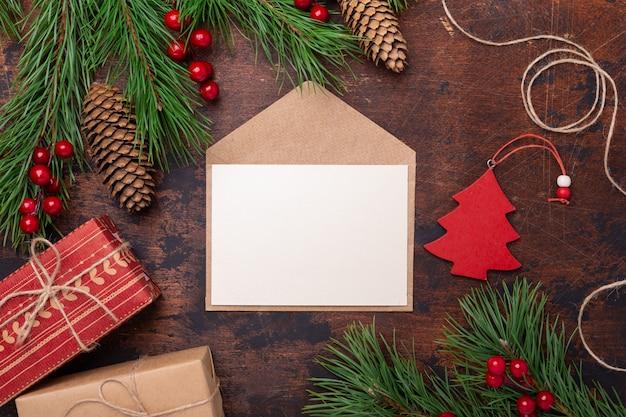 Biglietto di auguri di natale con ramo di abete, regali, confezione regalo e busta. vista dall'alto di sfondo in legno