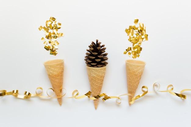Biglietto di auguri di natale festivo con decorazioni dorate, cialde commestibili, cono e glitter dorati.
