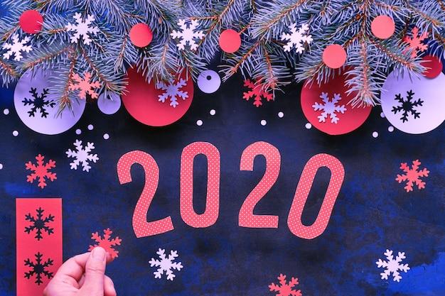 Biglietto di auguri di natale o capodanno con numero 2020, ramoscelli di abete, decorazioni in carta bianca e rossa