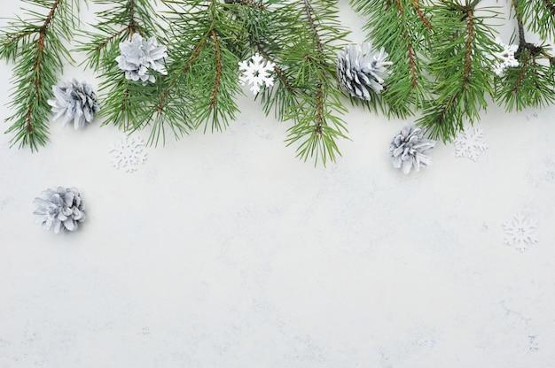 Biglietto di auguri di natale piatto laici con rami di abete e fiocchi di neve