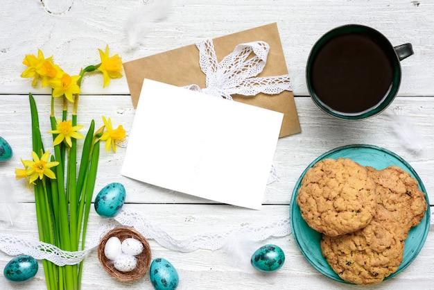 Biglietto di auguri di pasqua con uova di pasqua, fiori primaverili, tazza di caffè e biscotti per la colazione