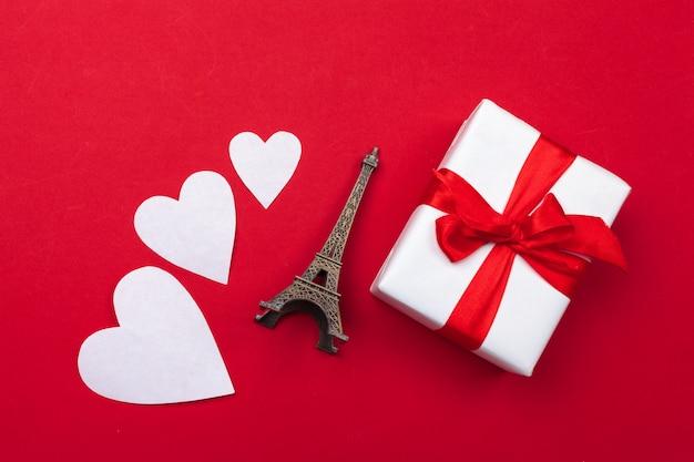 Biglietto di auguri di san valentino. confezione regalo sul tavolo rosso. vista dall'alto
