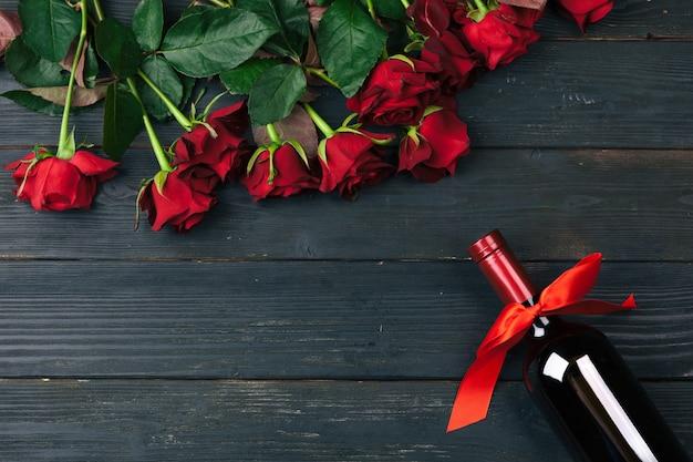 Biglietto di auguri di san valentino. fiori della rosa rossa, vino e contenitore di regalo sulla tavola di legno.