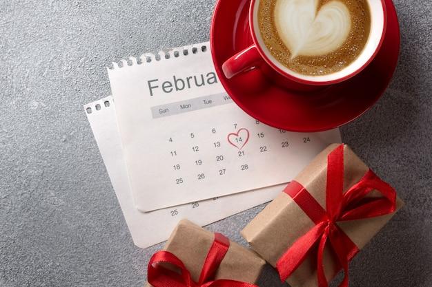 Biglietto di auguri di san valentino. tazza di caffè e contenitore di regalo rossi sopra il calendario di febbraio. vista dall'alto