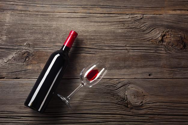 Biglietto di auguri di san valentino. vino rosso, confezione regalo e bicchieri sul tavolo di legno. visualizza con lo spazio per i tuoi saluti.