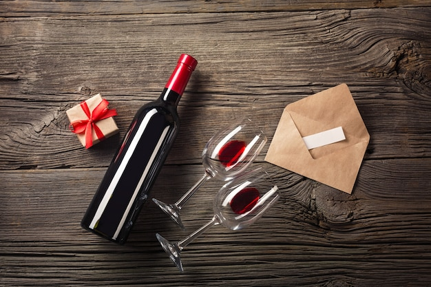 Biglietto di auguri di san valentino. vino rosso, confezione regalo e bicchieri sul tavolo di legno