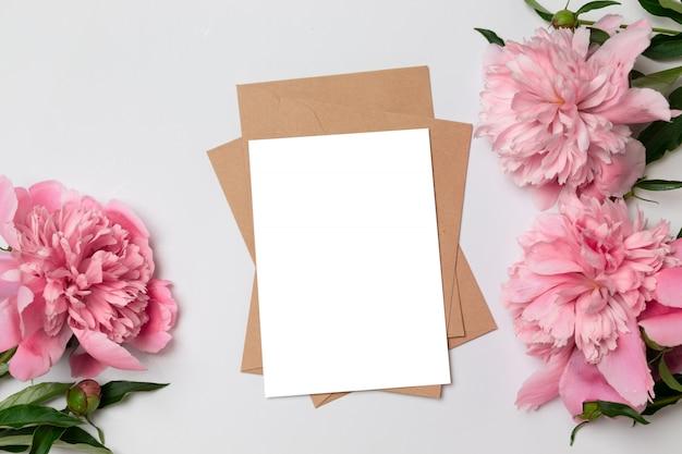 Biglietto di auguri minimalista layout con peonie rosa fiore, busta per cucito, fioritura, distesi, vista dall'alto